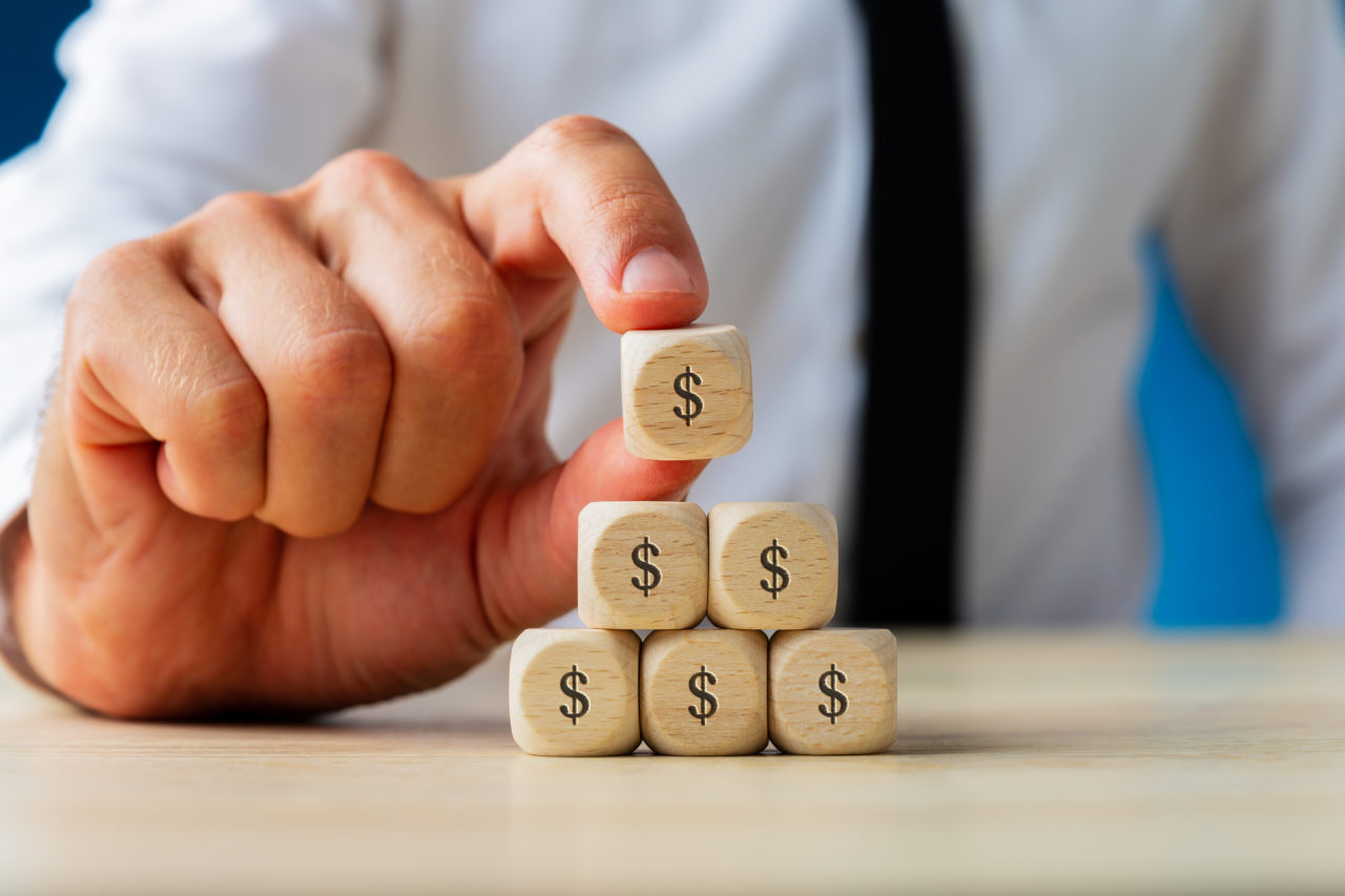 Business finance and economy concept - businessman making pyramid shape of wooden dices with dollar sign on them.